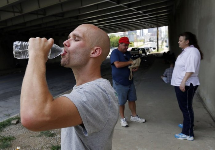 Terry Teague (background) of our Bible Study handing out water and cards to a couple living on the street. (Photo courtesy of Tulsa World)